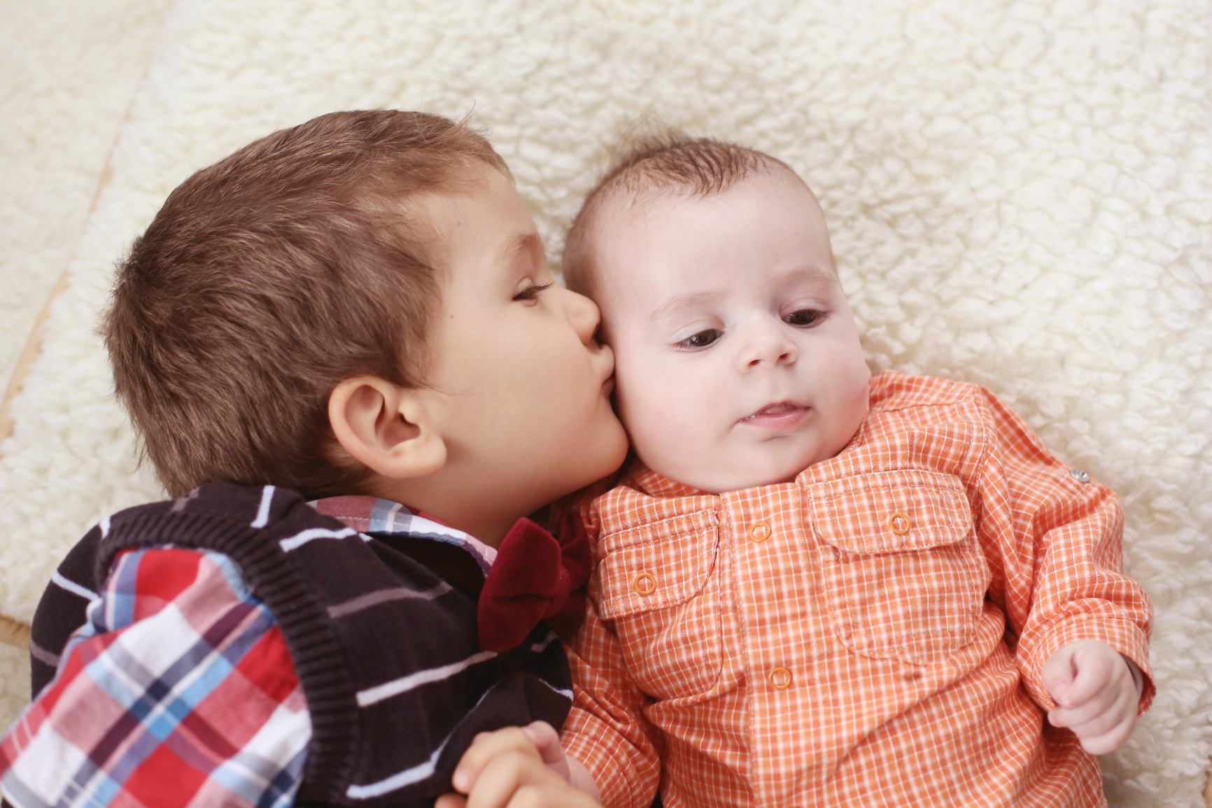 Big brother kissing the baby
